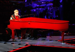 Elton John at a red piano
