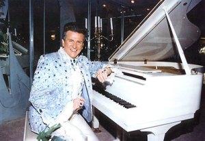 Liberace at a white piano